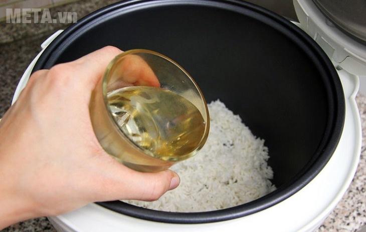 Đổ nước vào gạo để nấu cháo