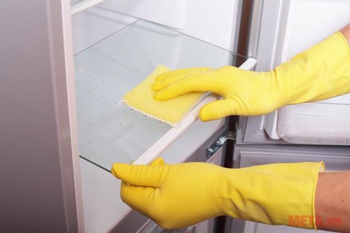 Tháo ngăn tủ rồi lau với hỗn hợp dấm trắng và nước